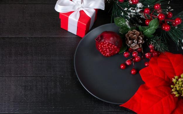 Fondo de año nuevo. flor de pascua de navidad granada roja y caja de regalo