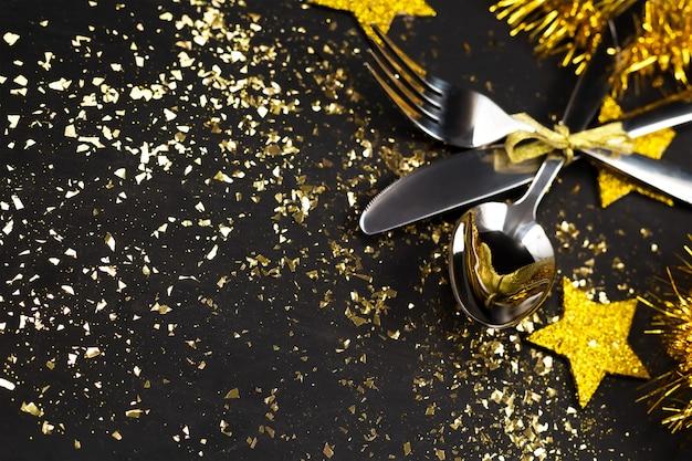 Fondo de año nuevo mesa negra con platería, estrellas doradas, oropel, decoración navideña.