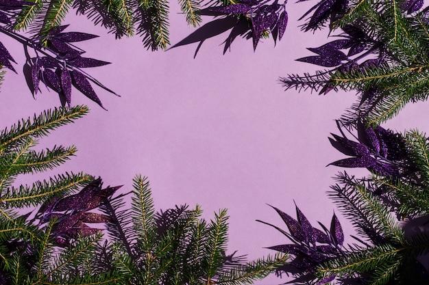 Fondo de año nuevo o festivo con elementos decorativos de ramas de abeto y hojas decorativas de color lila con lentejuelas. una copia del espacio.