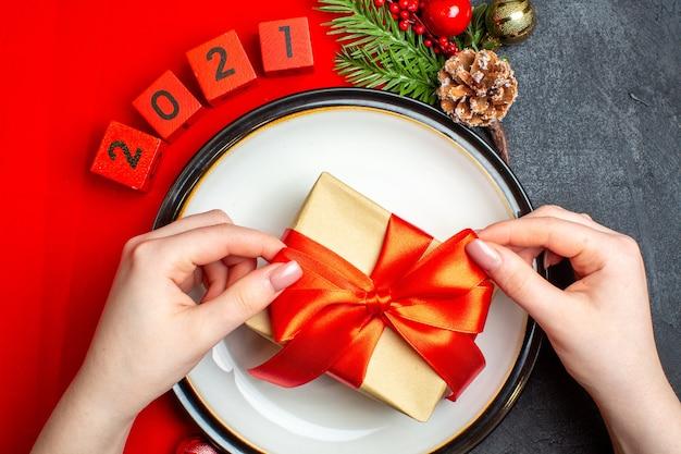Fondo de año nuevo con regalo en accesorios de decoración de plato de cena ramas de abeto y números en una servilleta roja sobre una mesa negra