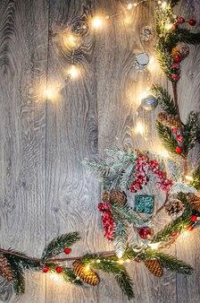 Fondo de año nuevo. sobre tablas de madera clara hay ramas de abeto, decoración de año nuevo, una caja con un lazo rojo. en la caja hay una figura de perro dorado y un bulto.