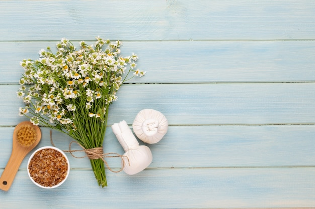 Fondo de aromaterapia spa, plano de varios productos de belleza decorados con flores de manzanilla simples.