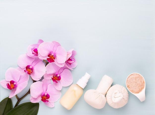 Fondo de aromaterapia spa, plano de varios productos de belleza decorados con flores de orquídeas simples.