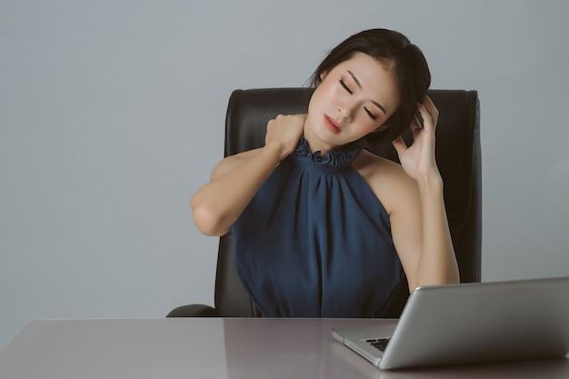 Fondo asiático de la oficina del dolor de hombro y del dolor de espalda de la mujer de negocios