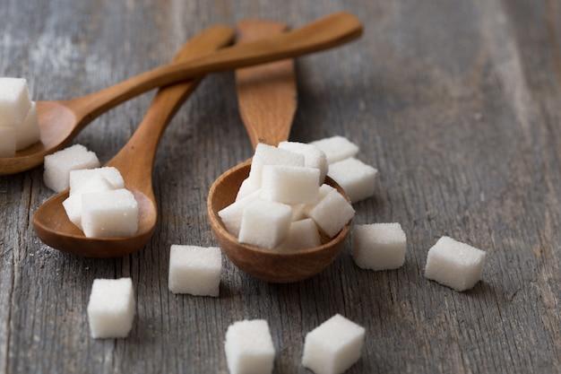 Fondo de azúcar terrones de azúcar, azúcar granulada en cuchara y plato. azúcar blanco sobre fondo gris de hierro galvanizado. copia espacio
