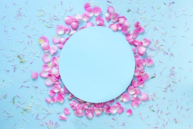 Fondo azul decorado con pétalos de flores frescas.