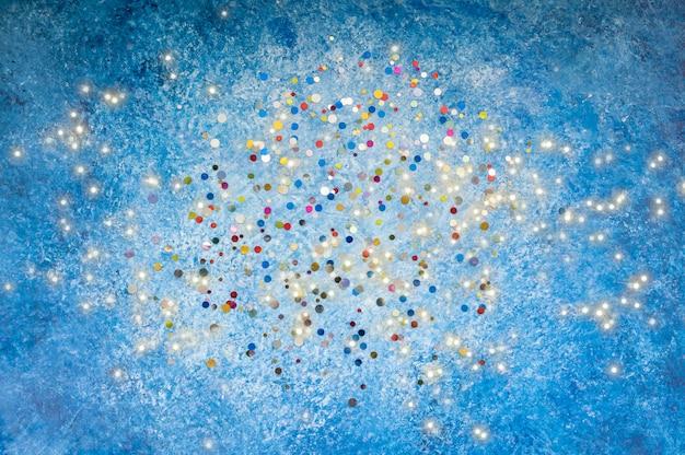 Fondo azul con lentejuelas de colores. vista superior, copia espacio. concepto de vacaciones.