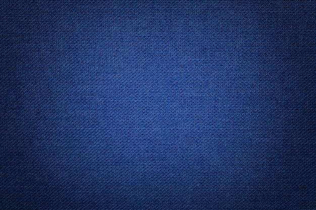 Fondo azul marino de un material textil con patrón de mimbre, primer plano.