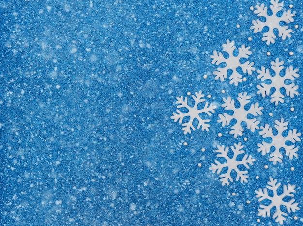 Fondo azul de navidad o invierno con copos de nieve blancos, perlas y nieve. concepto de navidad, año nuevo o invierno. estilo plano laico con espacio de copia.