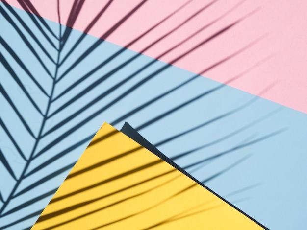 Fondo azul y rosa con una sombra de hojas y un espacio en blanco amarillo