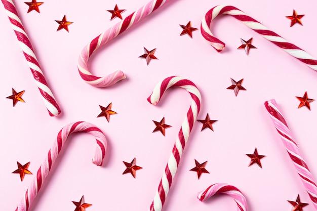 Fondo con bastones de caramelo de navidad, brillantes estrellas rojas en rosa