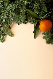 Fondo beige con borde de ramas de árboles de navidad y mandarina como símbolo de año nuevo