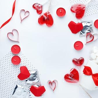 Fondo blanco con corazones rojos, condones, dulces y velas.