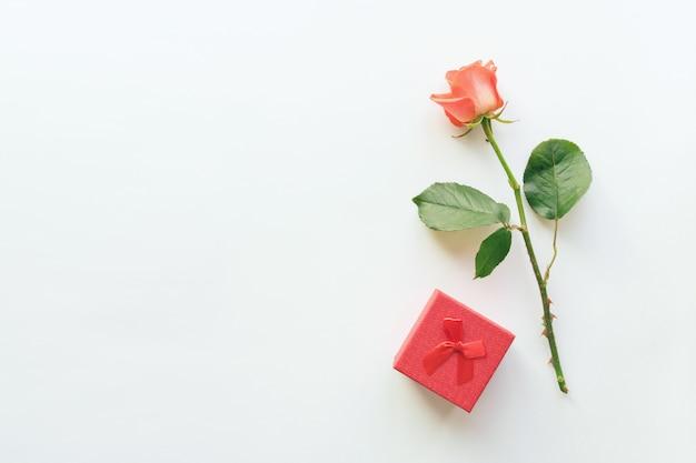 El fondo blanco cosmético de la belleza con el lápiz labial rojo, el rectángulo de regalo y se levantó