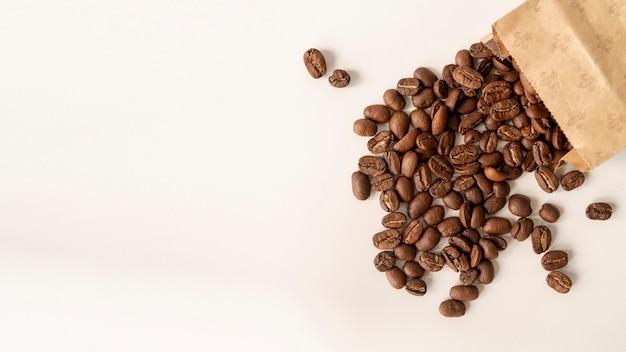 Fondo blanco con granos de café en bolsa de papel