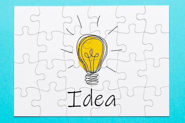 Fondo blanco del rompecabezas con el texto de la idea y el dibujo del bulbo