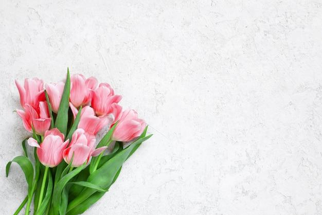 Fondo blanco con textura con tulipanes tiernos frescos