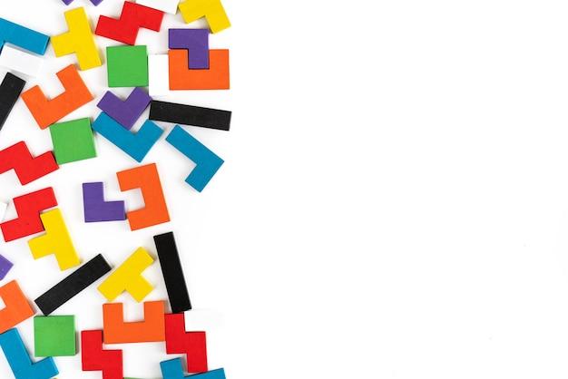 Fondo de bloques de madera de diferentes formas coloridas sobre fondo blanco. juguetes naturales y ecológicos para niños. concepto de pensamiento creativo y lógico. endecha plana. copia espacio