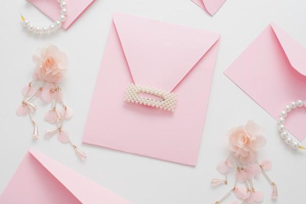 Fondo de boda, decorado con invitaciones rosas y joyas de perlas