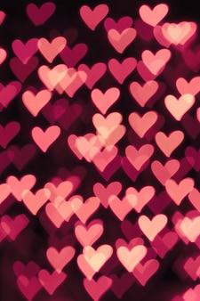 Fondo bokeh desenfocado con corazones de color rosa