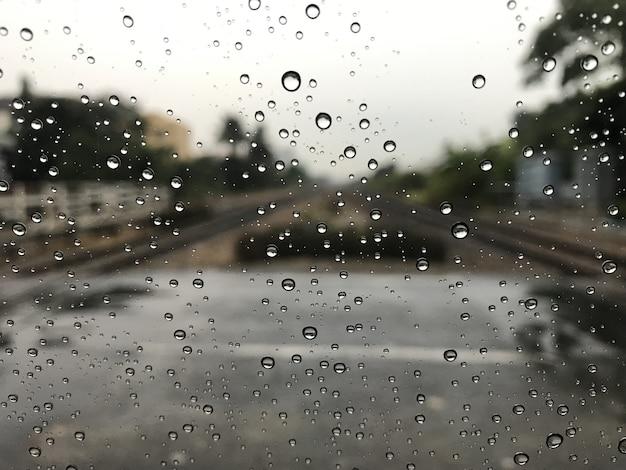 Fondo borroneado con lluvias caen sobre vidrios y coches en el ferrocarril