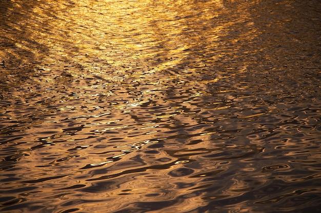 Fondo borroso de agua superficial en la hora del atardecer