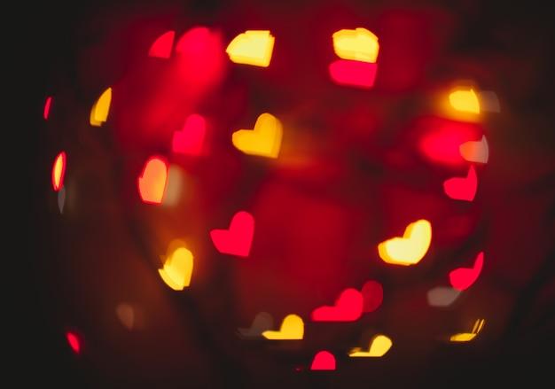 Un fondo borroso con bokeh en forma de corazones en diferentes colores. fondo desenfocado