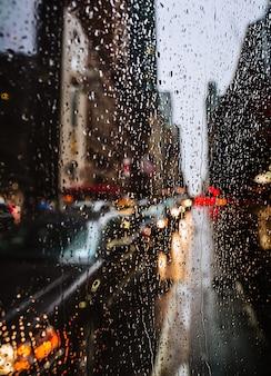 Fondo borroso de la calle de la ciudad de nueva york con gotas de agua, luces y coches al atardecer lloviendo