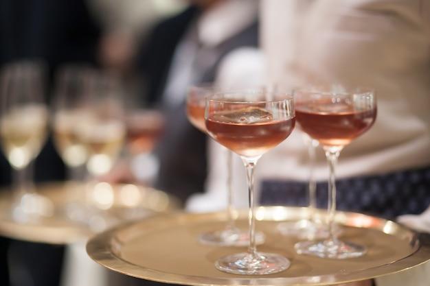 El fondo borroso del camarero sostiene la bandeja con una copa de champán para servir al cliente.