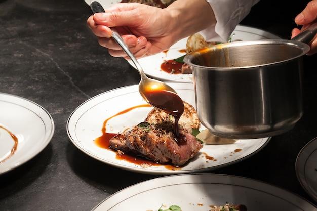 El fondo borroso del chef está vertiendo la salsa en la carne es el plato principal.