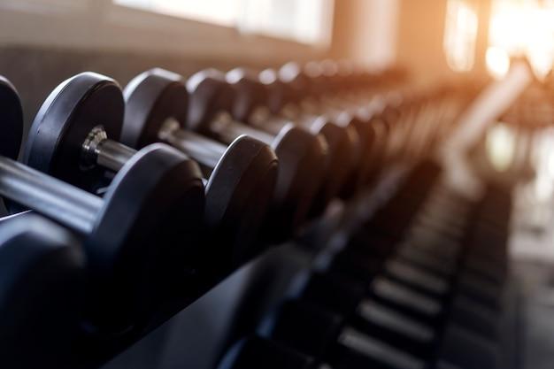 Fondo borroso de filas de pesas negras en el estante en el gimnasio.