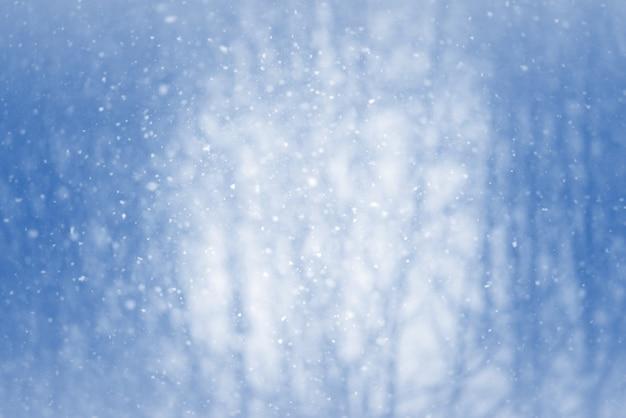 Fondo borroso de invierno con copos de nieve