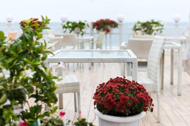 Fondo borroso, mesas y sillas vacías de un restaurante en una terraza con vistas al mar.