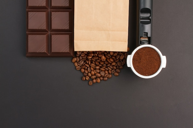 Fondo de café: espresso en un soporte, granos de café y una barra de chocolate