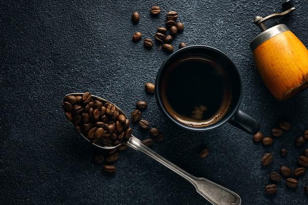 Fondo de café con granos de café, café y cuchara sobre fondo oscuro. vista desde arriba. concepto de café.