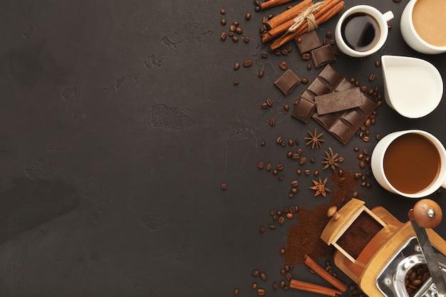 Fondo de café con tazas variadas, molinillo vintage, frijoles, especias y chocolate en pizarra negra, vista superior, espacio de copia. diseño horizontal para publicidad de cafetería o cafetería.