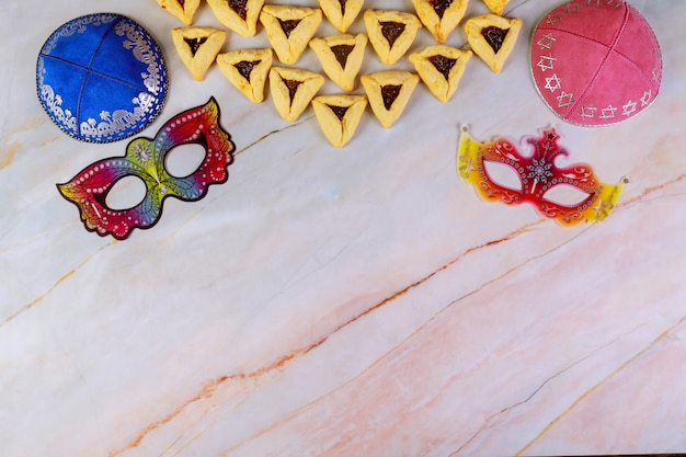 Fondo de carnaval de purim con kippa, máscaras y galletas.