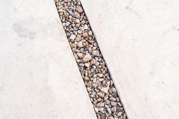 Fondo de cemento atravesado por una línea diagonal de guijarros de piedra