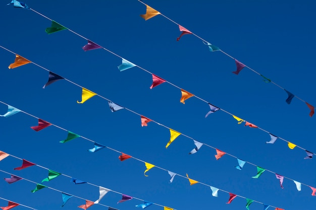Fondo de cielo azul con varias cuerdas con banderines de colores.