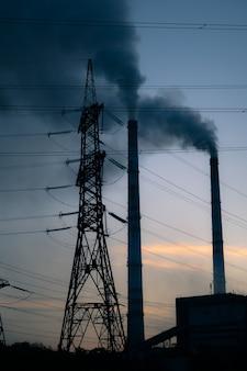 Fondo de cielo de torre de alta tensión, tubo de fábrica con humo sobre él