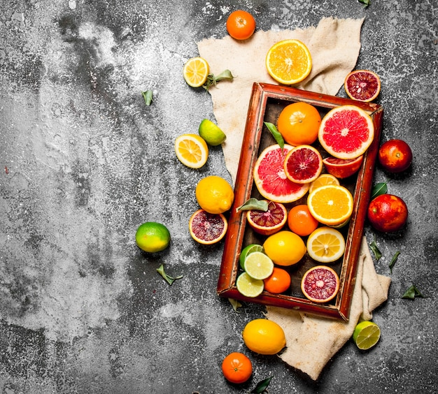 Fondo de cítricos. frutas cítricas en la bandeja vieja. sobre fondo rústico.