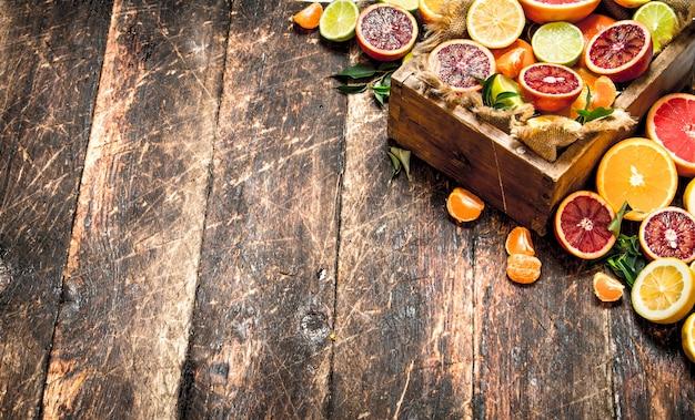 Fondo de cítricos. frutas cítricas en una caja vieja. sobre fondo de madera.