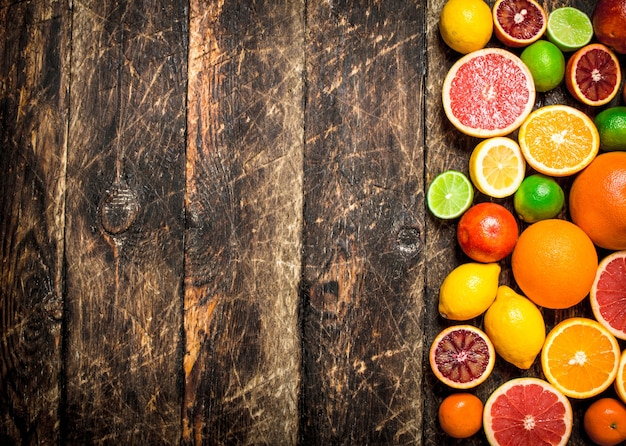 Fondo de cítricos. frutas cítricas frescas: limones, naranjas, limas, pomelos. sobre fondo de madera.