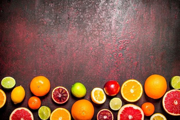 Fondo de cítricos. frutas cítricas . sobre fondo rojo rústico.