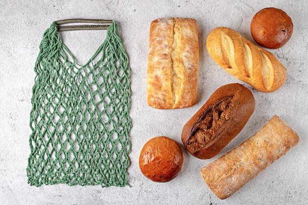 Fondo de cocción con bolsa de hilo ecológico y panes de pan recién horneados enteros vista superior sobre fondo gris