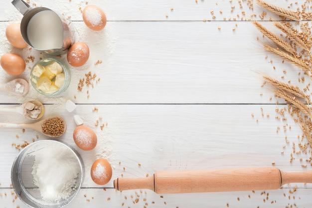 Fondo de cocción. cocinar ingredientes para masa de levadura y pastelería, huevos, harina y leche en madera rústica blanca. vista superior