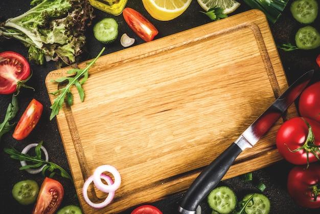 Fondo de cocción, ingredientes para ensaladas frescas, cocina italiana: tomates, aceite de oliva, limón, pepinos, rúcula, perejil, cebolla, con cuchillo y tabla para cortar
