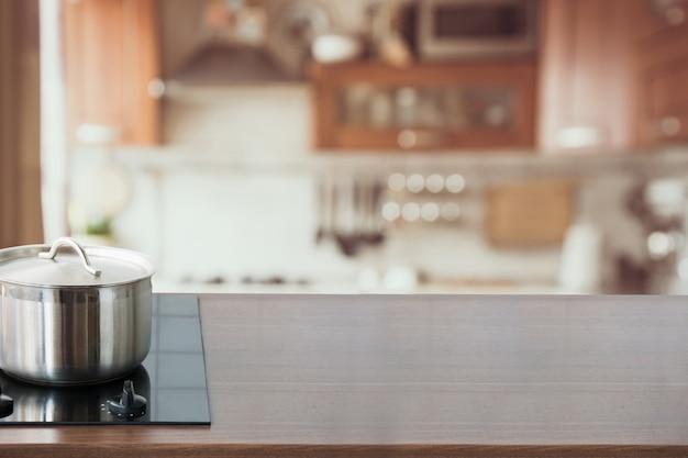 Fondo de cocina borrosa y abstracta. tablero de madera con sartén y cocina moderna desenfocada.