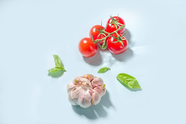 Fondo de cocina de comida mediterránea, tomates frescos, albahaca, aceite de oliva y ajo sobre fondo azul