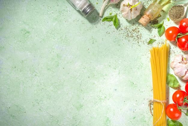 Fondo de cocina de comida mediterránea, tomates frescos, albahaca, aceite de oliva y ajo sobre fondo verde claro